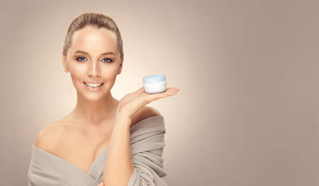 Young woman with skin cream for face in hand, look to you, close up portrait on beige isolated with free copy space.