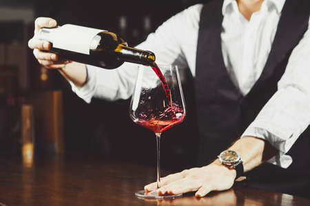 Close-up photo, sommelier pours red wine to glass on bar counter background. Banco de Imagens