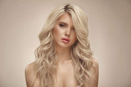 Pretty young blonde woman with nude makeup has a curly long bright hair, close up portrait on beige isolated Banco de Imagens