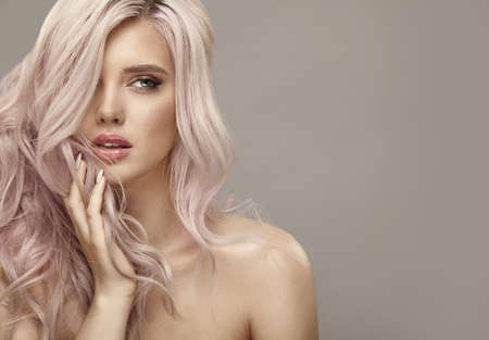Much attractive woman with long healthy curly hair of pink color on beige isolated with free copy space