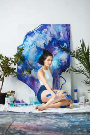 Young artist creates new artwork sitting on floor. Serious woman