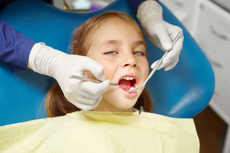 Work of dentist with young patient. Survey of the teeth of small child. Banco de Imagens