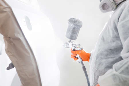 Painting the car in the paint room, spray gun with white paint.