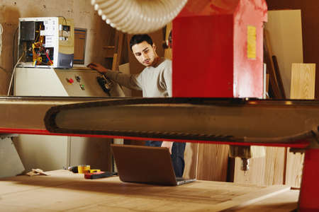 Woodworker operates the machine with program numerical control. Cnc router.