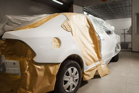 Garage painting car service. vehicle cover with protective paper before painting.