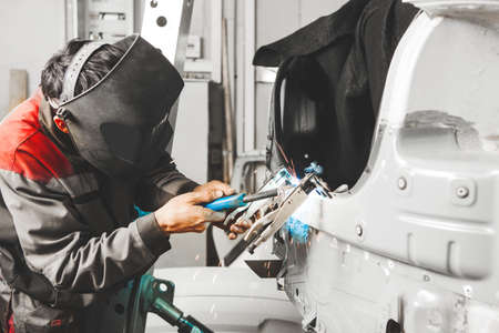 Working with carbon dioxide welding to fix metal body. Repair service worker recovery damaged car. Welder, weld.