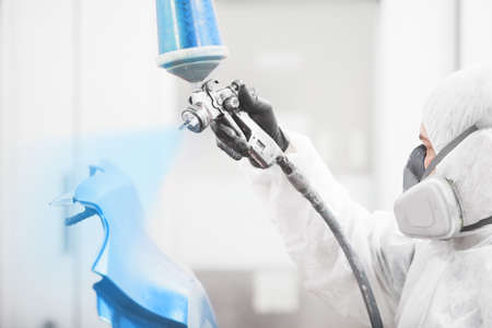 Man sprays blue dye on the elements of the vehicle.