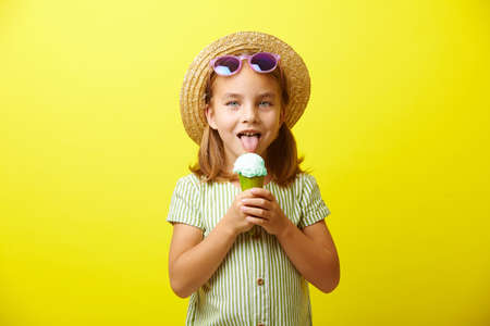 Little caucasian girl in green dress and straw hat, eating beautiful ice cream, wears blue sunglasses, has a good mood, stands on yellow isolated.