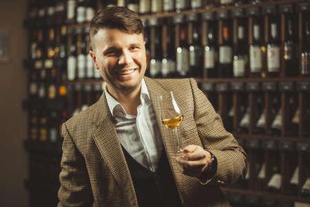 Smiling sommelier in the wine cellar tasting whiskey.
