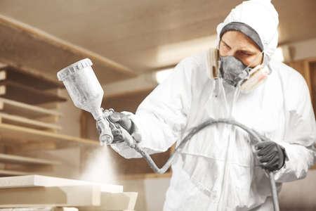 Man in respirator mask painting wooden planks at workshop. Banco de Imagens