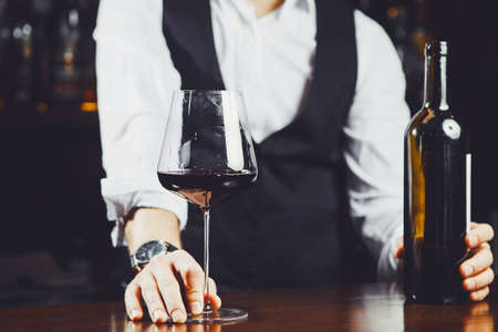 Bartender at the bar with a glass of red wine and bottle, close-up.