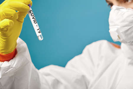 Doctor in protective clothing hold medical tube with a smear for sample results coronavirus. Corona virus outbreaking.