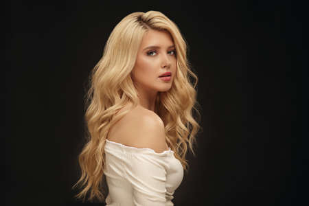 Blonde woman portrait, attractive adult girl in studio over black background