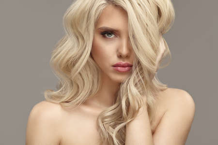 Beautiful girl with volume wavy long hair blonde has a natural hairstyle of wavy curly