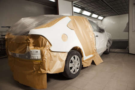 Body repair of the car after the accident. Wraping of vehicle with protective paper before painting. Banco de Imagens