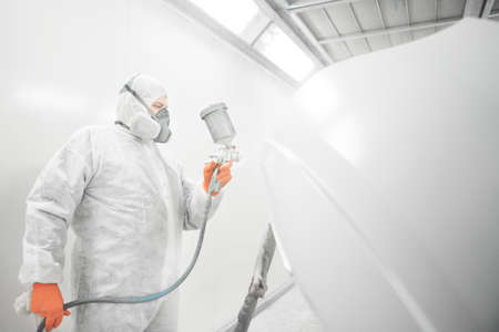 Worker spraying white paint with spray gun on car. Banco de Imagens