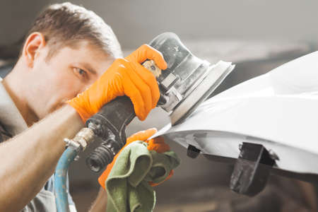 Auto mechanic grinds white car part after painting before polishing, close-up.