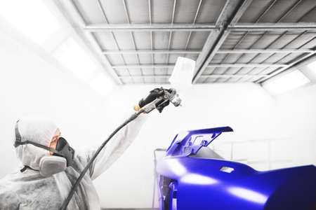 Male worker sprays varnish with spray gun on car element after painting. Banco de Imagens