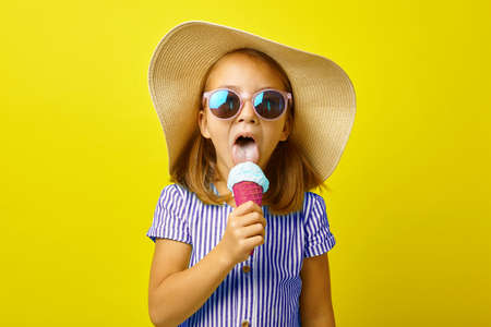 Funny little girl in summer clothes eating beautiful ice cream, standing on yellow isolated background.