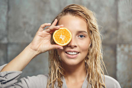 blonde caucasian female model with a piece of orange near her face, close up shot in the bathroom.