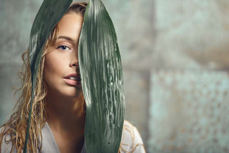 Beautiful young woman wearing a bathrobe in the bathroom with wet hair holds large green tropical leaves in her hands and covers part of her face.