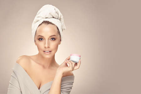 Female beauty model after a shower holds near her face natural eco safety cream on beige isolated, close up portrait with free copy space. Banco de Imagens