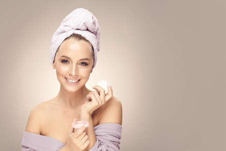 Beautiful smiling female model with clean skin, wearing in bathrobe and towel on head, hold cream on beige isolated with free copy space.