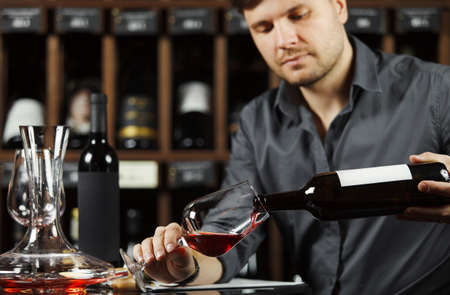 Sommelier pouring red wine from bottle in glass Banco de Imagens