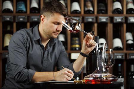 Sommelier degustating red wine poured in glass Banco de Imagens