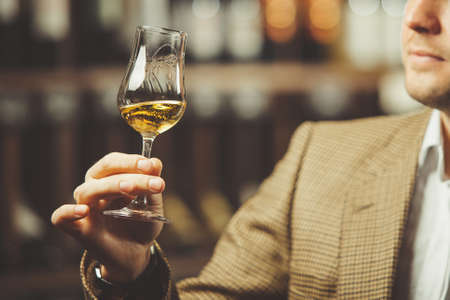 Sommelier holding a glass of whiskey, evaluates the color, smell and taste of alcoholic beverage.