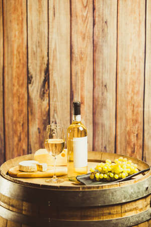 Vertical shot of white wine in glass, bottle, grape and cheese on barrel over wood wall.