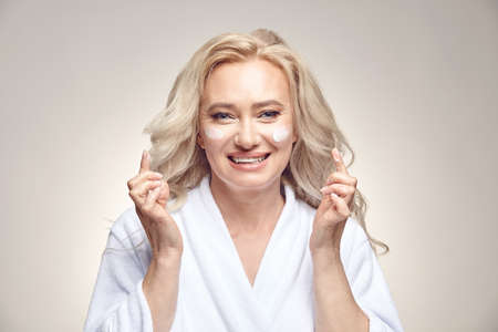 Joy smiling middle aged woman in white bathrobe applies cream to her face on beige isolated close up portrait. Stock Photo