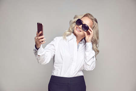 Smiling mature woman trying on sunglasses and taking selfies, portrait on gray isolated of senior lady in a stylish casual look