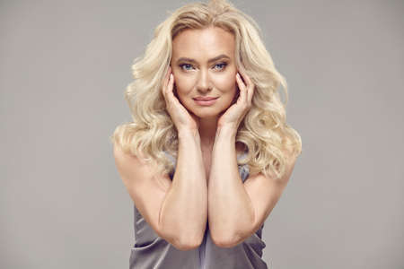 Beauty blonde senior woman with a curly blonde hair and healthy skin on a grey isolated