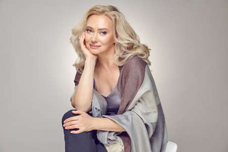 Beautiful female mature age feels good. Middle aged blonde woman with a great looking wearing in stylish casual clothing and stole blanket looks to camera on a beige isolated. Standard-Bild
