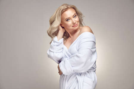 Caucasian mature blonde woman with a clean a healthy skin, wearing in spa bathrobe over grey isolated background.