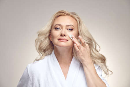 Good looking mature woman in spa bathrobe applies cream to the face over beige isolated.