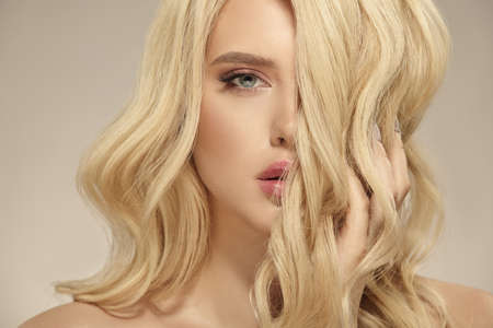 Female beauty, hairstyle of blonde long wavy hair. Caucasian attractive woman has a natural curly hairstyle, close up shot on a beige isolated.