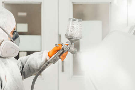 Male worker sprays paint with spray gun on car body part in car maintenance service paint room. Banque d'images