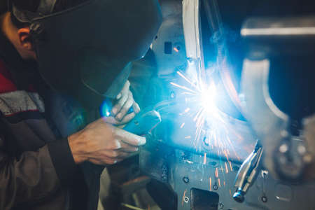 Professional car body repair, welding of auto body. Industrial worker welds metal elements of vehicle. Banque d'images