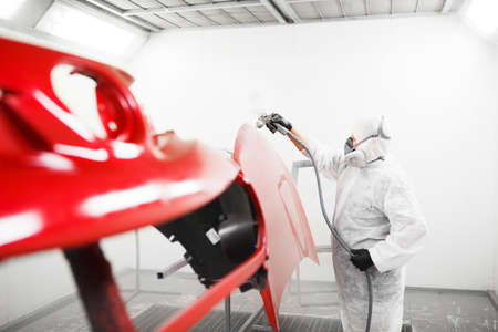 Car painter sprays varnish in paint booth. Banque d'images