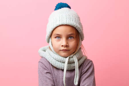 Close up studio portrait of cute frozen little girl with a big eyes wearing knit winter clothes over pink background.