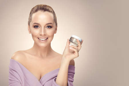 Smiling woman holds in hand skin cream for face over beige isolated with free copy space.