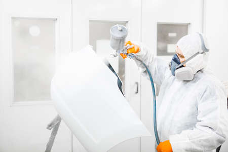 Body painter with airgun spraying white paint on a automobile in car maintenance service paint room.