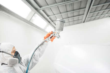Male repairman painter in chamber painting automobile car elements. Worker paints the vehicle in white with a spray gun.