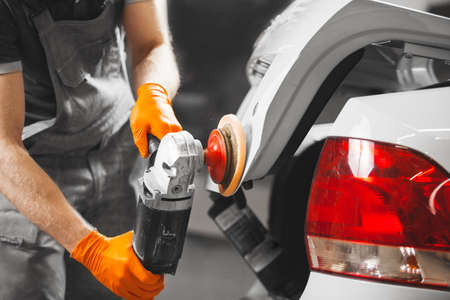 Buffing of white car, worker with polishing machine recovers bodywork. Automobile detailing.