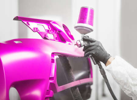 Professional male car painter is painting in garage by airbrush. Man works with spray gun. Banque d'images