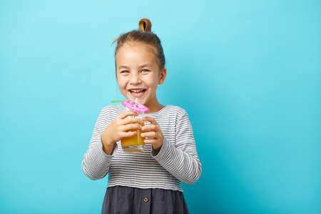 Cheerful little girl drinks orange juice and laughs, stands on blue isolated background.