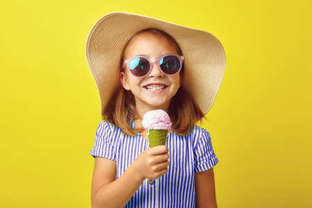 Cheerful little girl with ice cream on yellow isolated background. Banque d'images