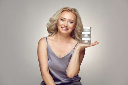 Smiling older woman holding various jars of cream over grey isolated